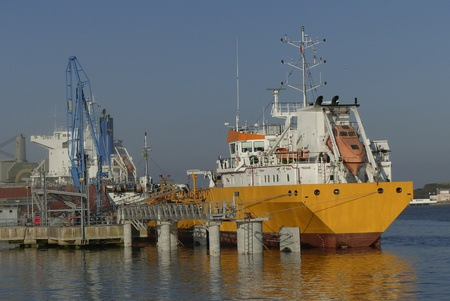 Products Tanker discharging at the Oil Terminal of Lorient France. Horizontal stern view, yellow hull and white funnel on blue sky background