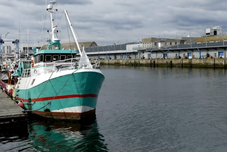 trawler net: Turquoise Fishing boat alongside the pier at the fishing harbor of Lorient, Brittany, France. Horizontal view from bow