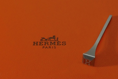 Lorient, France - March 17, 2017: Hermes Paris logo with horseshoe nail on house Hermes orange color background is a famous french luxury brand Existing since 1837 ..
