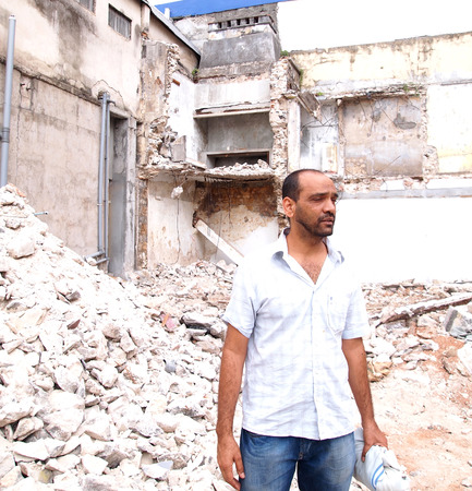 ravaged: Syrian man in front of rubble Editorial