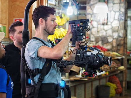 Man using cinema camera with backpack stabilizer in market