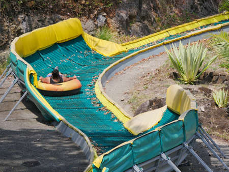 People gliding down on rubber at amusement park Banque d'images