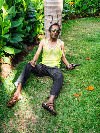 Drunkard resting down under a tree with bottle in hand on the grass Éditoriale