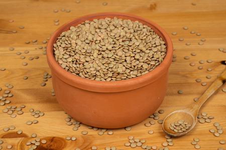 Green lentils in a pot with a wooden spoon on a wooden surface Archivio Fotografico - 108115891