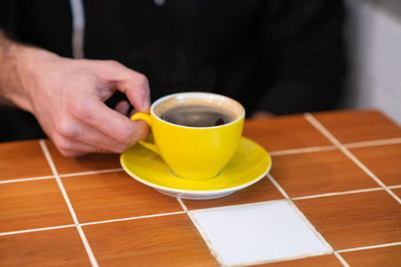filter coffee in a yellow cup, held by man hands. black coffee with man hands shown.