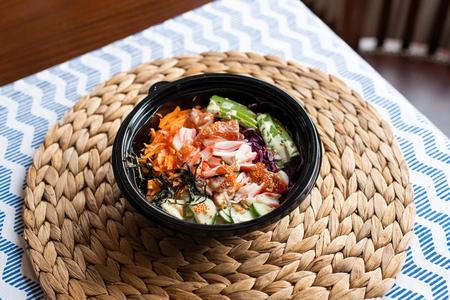hawaii poke bowl with salmon, rice, surimi, avocado, tobiko, carrot and seaweed Reklamní fotografie