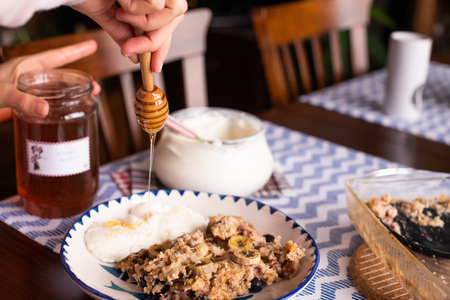 preperation of baked oatmeal with banana, blueberries, walnut and raisins. served with yoghurt and honey. dripping honey. putting yoghurt. Reklamní fotografie