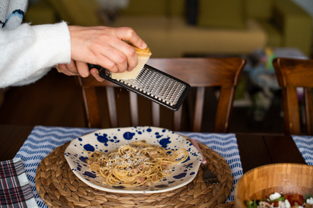 woman hands grating parmesan cheese on pasta carbonara 版權商用圖片
