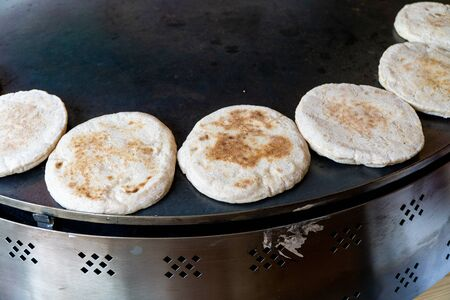 Baking pita bread, small fluffy breads. Also known as pide or bazlama. Showing multiple small breads