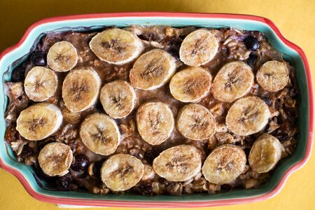 Baked oatmeal with bananas, blueberries, and walnuts. served in stoneware