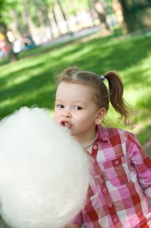 algodon de azucar: niña comiendo algodón de azúcar en el parque