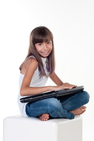 young girl barefoot: Cute little girl is sitting with laptop, isolated over white