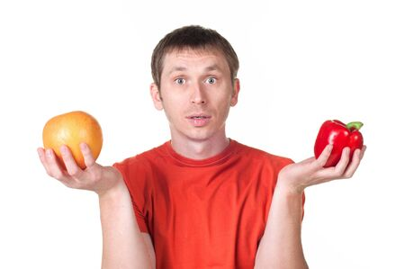 young man hold in his hand fresh pepper and grapefruit, isolated on white Stock Photo - 21175984