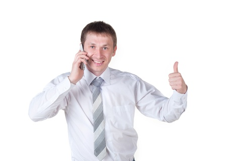 young business man showing thumbs up sign and speaking at the phone while smiling to the camera on a white background Stock Photo - 21203376