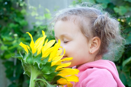 Beautiful little girl and sunflower, outdoor portrait