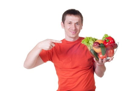 Young man with plate of fresh healthy vegetables on white background photo