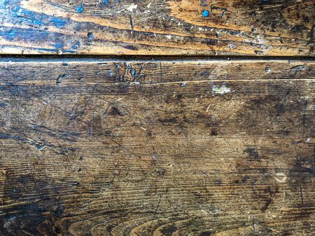 Dark wooden surface of an old desk. Oak planks with aged effect. Antique furniture texture.Wooden tabletop with scratches and stains.