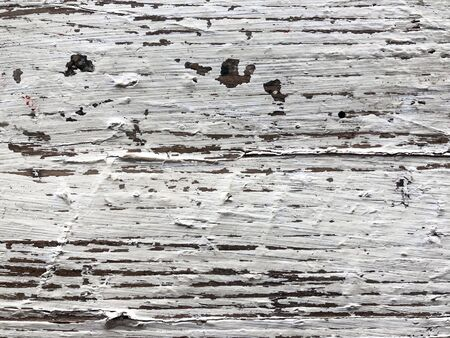 Embossed texture of an old painted wooden board. White board with cracks and scratches. Aged oak surface with a beautiful natural texture. Horizontal fibers of a tree. Vintage background in provence style 免版税图像