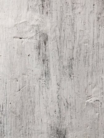 Embossed texture of an old painted wooden board with building plaster on it. White board with scratches. Dirty surface with interesting texture. Vertical fibers of a tree. Vintage background in provence style 免版税图像