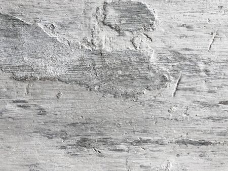 Embossed texture of an old painted wooden board with building plaster on it. White board with scratches. Dirty surface with interesting texture. Horizontal fibers of a tree. Vintage background in provence style