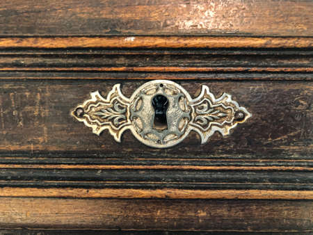 Antique keyhole in a rare chest. Dark wooden surface of an old desk. Oak planks with aged effect. Antique furniture texture.Wooden tabletop with scratches and stains.