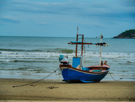 A fisherman Boat is lining on beach with background wave and blue sky. Stock Photo