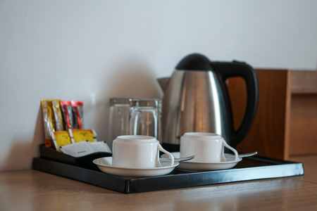 beverage set with coffee cup, kettle, glasses, tea, coffee, sugar in hotel room