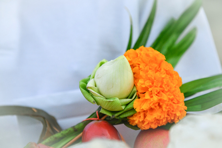 person wear white go to temple with lotus and orange flower make merit