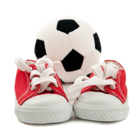 Red baby sneakers with a ball isolated on white background  Stock Photo