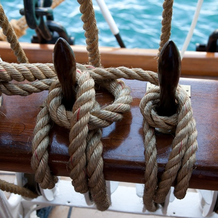 Two ropes control the sails, tied to a wooden beam photo