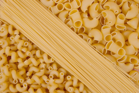 various shapes of uncooked pasta background  photo