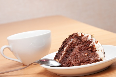 tasty chocolate cake on a plate with a cup of coffee photo