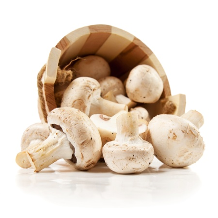 mushrooms champignon scattered from a wooden bucket  isolated on a white background Stock Photo