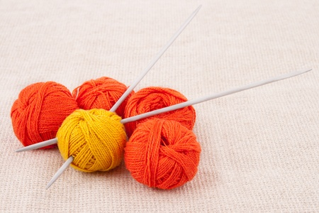 Bright balls of yarn with knitting needles on the canvas fabric