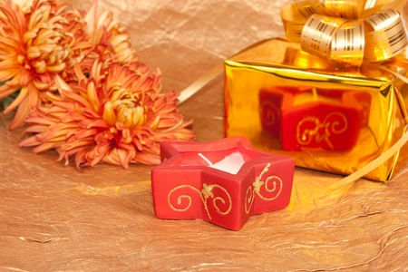 chrysanthemum, gift and red candle on gold background  photo