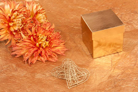 two handmade hearts and gift box on gold background  photo