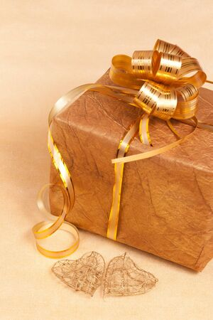 two handmade hearts and gift box on gold background close up photo