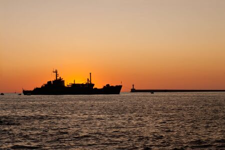 The silhouette of a ship floating on the sea at sunset
