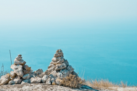 Two pyramids of stones against the blue sea background Stock Photo - 16456802