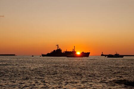 The silhouette of a ship floating on the sea at sunset  photo