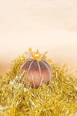 Christmas background with a ball and a tinsel on gold