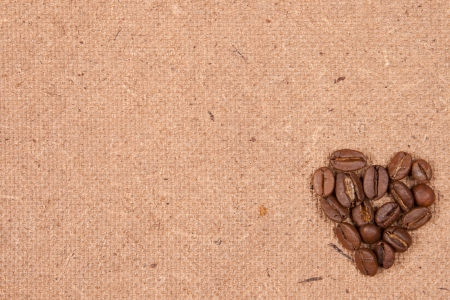 coffee beans on textured old paper spilled in the form of heart scrapbooking background photo