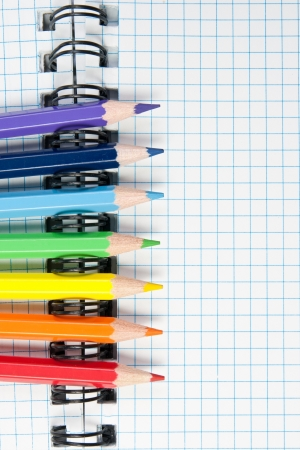 Colored pencils and a notebook background Stock Photo