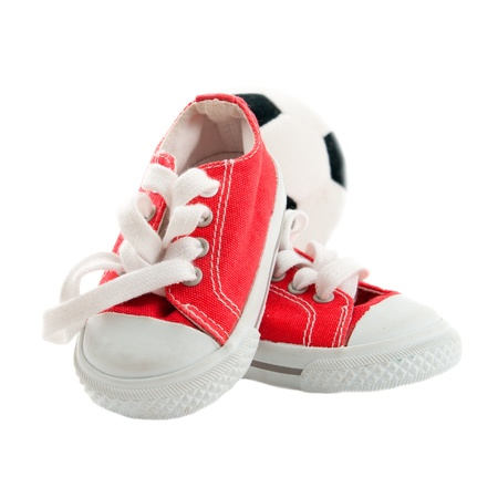 Red baby sneakers with a ball isolated on white background  photo