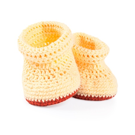 Handmade sweet baby booties isolated on a white background  photo