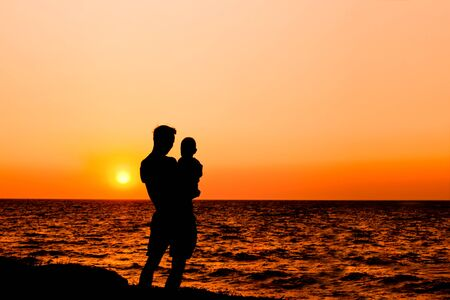 father and son at sunset sea closeup photo
