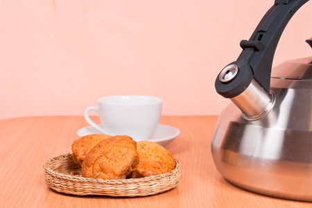 Close up of  kettle, cup and cakes with light background
