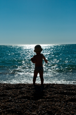 a little boy play at sunset sea close up Stock Photo