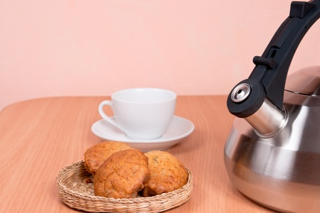 Close up of  kettle, cup and cakes with light background photo