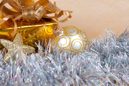 Christmas background with a gift box and a tinsel on gold  Stock Photo